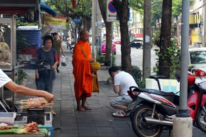 Un moine qui reçoit un offrande